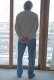 Anziano che osserva fuori sopra il paesaggio nevoso. Fotografia Stock