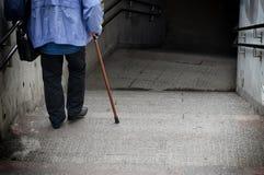 Anziano che scende scale Fotografie Stock Libere da Diritti