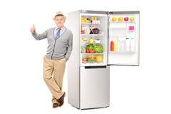 Anziano che si appoggia un frigorifero e che dà pollice su Fotografia Stock