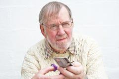 Anziano che taglia una carta di credito. fotografia stock