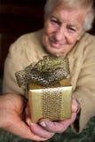 Anziano che tiene un contenitore di regalo Fotografie Stock Libere da Diritti
