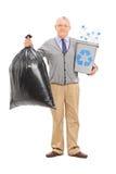 Anziano che tiene un recipiente di riciclaggio e una borsa di immondizia Fotografie Stock Libere da Diritti
