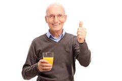 Anziano che tiene un succo e che dà un pollice su Immagini Stock Libere da Diritti