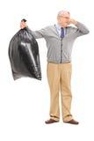 Anziano che tiene una borsa di immondizia puzzolente Immagine Stock Libera da Diritti