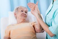 Anziano con il braccio doloroso immagine stock