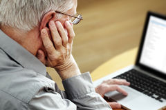 Anziano con il computer portatile Fotografia Stock