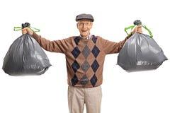 Anziano con le borse di immondizia immagine stock libera da diritti