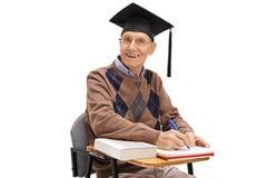 Anziano con un cappello di graduazione che si siede in una sedia della scuola Fotografia Stock