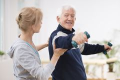 Anziano dopo il colpo alla casa di cura che si esercita con il fisioterapista professionista immagini stock libere da diritti