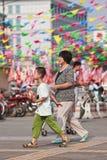 Anziano femminile con il nipote nella zona commerciale, Pechino, Cina Immagini Stock
