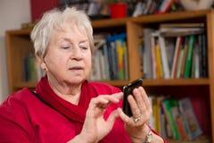 Anziano femminile con lo smartphone Fotografia Stock