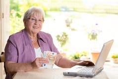 Anziano femminile con soldi ed il computer Immagini Stock Libere da Diritti