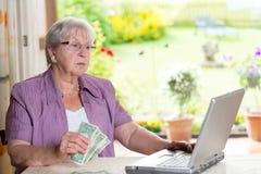 Anziano femminile con soldi ed il computer Fotografie Stock