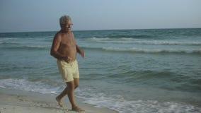Anziano maschio americano caucasico felice che gode del suo stile di vita all'aperto che balla sulla spiaggia U.S.A. 4k video d archivio
