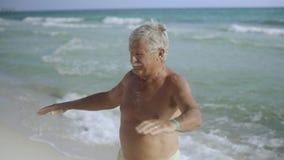 Anziano maschio americano caucasico felice che gode del suo stile di vita all'aperto sulla spiaggia e che fa U.S.A. eexercising 4 video d archivio