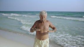 Anziano maschio americano caucasico felice che gode del suo stile di vita all'aperto sulla spiaggia e che fa U.S.A. eexercising 4 archivi video