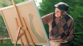 Anziano messo su una sedia che paiting su una tela stock footage