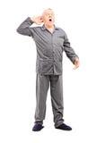 Anziano sonnolento nell'allungamento dei pigiami Fotografia Stock Libera da Diritti