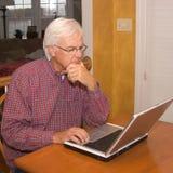 Anziano sul computer portatile Fotografie Stock