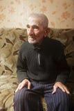 Anziano sul sofà che osserva obliquamente immagini stock libere da diritti