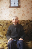 Anziano sul sofà sotto l'orologio Fotografie Stock Libere da Diritti