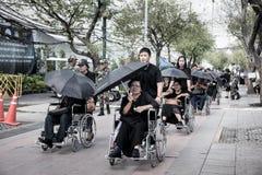 Anziano tailandese di aiuto del peope sulla sedia a rotelle alle devozioni per il funerale di fotografia stock libera da diritti