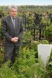Anziano triste che si leva in piedi tomba vicina immagine stock