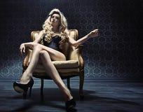 Anziehende blonde Dame, die auf einem Weinleselehnsessel sitzt Stockbild