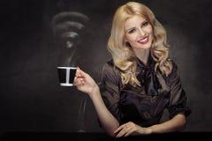 Anziehende blonde Frau, die den Kaffee mit dem WiFi-Zeichen stea trinkt Stockfotografie