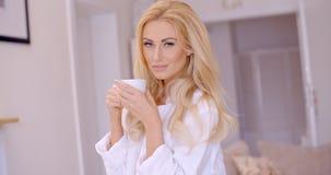 Anziehende blonde Frau mit dem Kaffee, der Kamera betrachtet Lizenzfreie Stockbilder