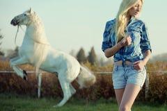Anziehende blonde Schönheit mit majestätischem Pferd Lizenzfreie Stockfotos