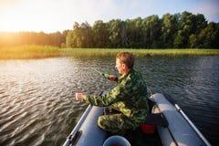 Anziehende Fische des Fischers auf dem Fluss vom Gummiboot liebhaberei lizenzfreie stockfotografie