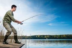 Anziehende Fische des Fischers, die am See angeln Stockfotografie