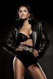 Anziehende Frau in der schwarzen Kleidung, die über dunklem Hintergrund aufwirft Lizenzfreie Stockbilder