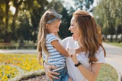 Anziehende Mutter, die nett sich fühlt, ihr Mädchen vom Kindergarten nehmend stockfoto