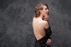 Anziehende reizend junge Frau im schwarzen Kleid mit offenem Rücken Stockbilder