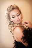 Blonde sexy Frau im Abendkleid im Luxusinnenraum. Stilvolles reiches dünnes Mädchen mit Frisur und hellem Make-up in der Wohnung. Stockbild