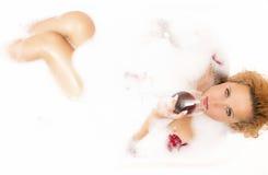 Anziehende sexy kaukasische blonde Frau in der schäumenden Badewanne gefüllt mit den blumigen Blumenblättern, die ein Glas Rotwei Stockfotografie