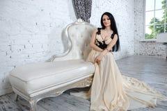 Anziehender Brunette, der auf Sofa im Luxusinnenraum sich entspannt Lizenzfreie Stockfotografie