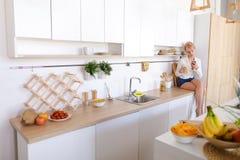 Anziehender weiblicher haltener Handy- und essenapfel, an sitzend Stockbilder