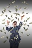 Anziehendes Geld des aufgeregten Mannes, das um ihn fällt Stockfoto
