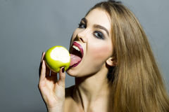 Anziehendes lächelndes blondes Mädchen mit Apfel Stockfoto