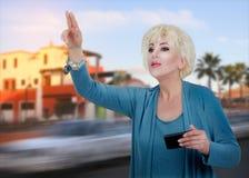 Anziehendes Taxi der erwachsenen Geschäftsfrau Stockbilder