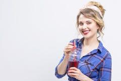 Anziehendes und glückliches kaukasisches blondes Mädchen, das in überprüftem Hemd-und Stirnband-trinkendem Saft aufwirft Stockbilder