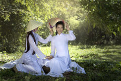 Ao Dai vietnam traditional dress. Two women in Ao Dai vietnam traditional dress under tree Stock Images