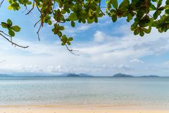 Ao Kao White Sand Beach is a hideaway beach with clean white sand, blue sea and bright sky with tree branches in foregroundใ. Ao Kao White Sand Beach is a royalty free stock photo