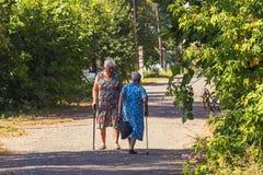Ao longo da rua são umas mulheres mais idosas com uma varinha especial para as pessoas idosas pensioners imagens de stock