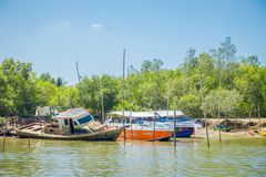 AO NANG,泰国- 2018年2月19日:两条豪华小船室外看法停放了接近一条被破坏的和老生锈的小船 免版税库存图片