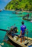 AO NANG,泰国- 2018年3月05日:关闭小船的未认出的人接近有一块华美的绿松石的一个马达 免版税图库摄影