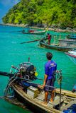 AO NANG,泰国- 2018年3月05日:关闭小船的未认出的人接近有一块华美的绿松石的一个马达 免版税库存图片